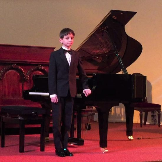 boy wearing a suit standing next to a grand piano