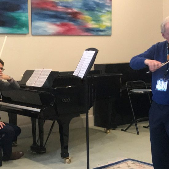 grey haired man playing violin with a girl playing violin and boy sitting at piano