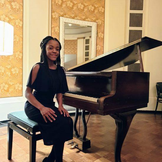 girl sitting at a baby grand piano, smiling at camera