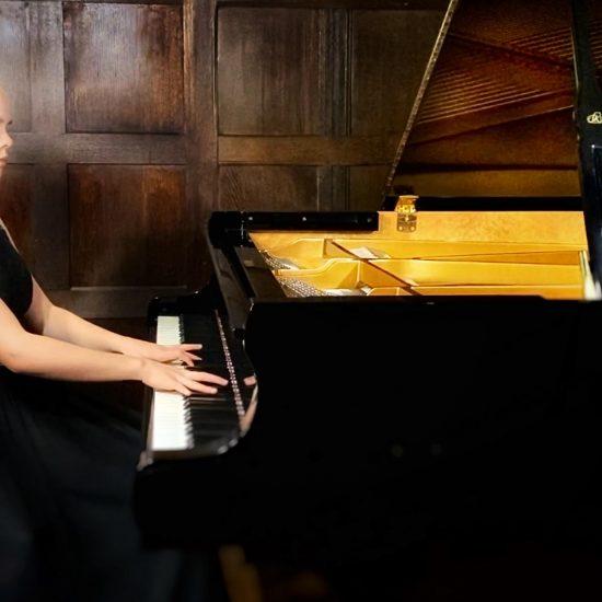 teenage girl playing a grand piano